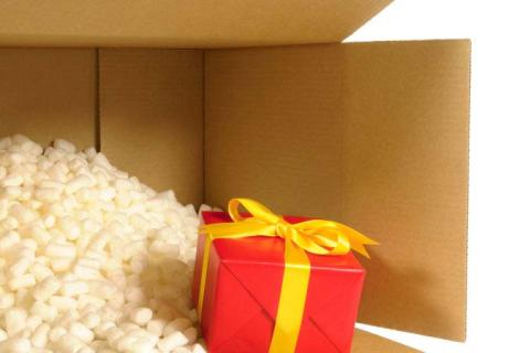 A wrapped present being shipped in a brown box with peanuts